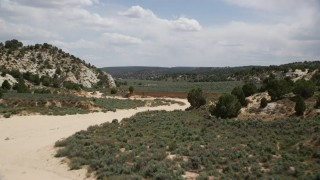 AX131_063 - 6K stock footage aerial video of flying over the edge of dry riverbed, Grand Staircase-Escalante National Monument, Utah