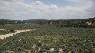 AX131_064 - 6K stock footage aerial video of flying low over vegetation near hills, Grand Staircase-Escalante National Monument, Utah