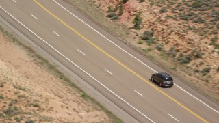 AX131_078 - 6K stock footage aerial video of tracking SUV on Highway 89, Glen Canyon National Recreation Area, Utah, Arizona