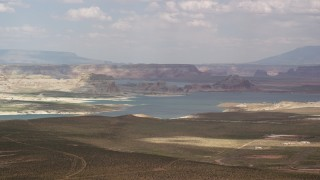 AX131_125 - 6K stock footage aerial video of flying by Lake Powell, Glen Canyon National Recreation Area, Utah, Arizona