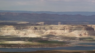AX131_128 - 6K stock footage aerial video of flying by mesa and Lake Powell, Glen Canyon National Recreation Area, Utah, Arizona