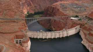 AX131_135 - 6K stock footage aerial video of flying by Glen Canyon Dam and Bridge, Arizona, zoom to wider view