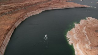 AX131_149 - 6K stock footage aerial video tilt to bird's eye view of a boat on Lake Powell in Arizona