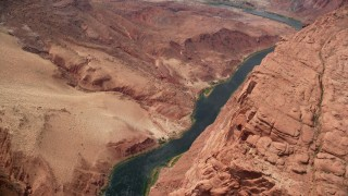 AX131_191 - 6K stock footage aerial video bird's eye view of the Colorado River at the base of rugged cliffs, Glen Canyon, Arizona