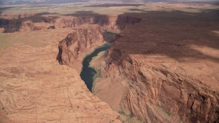 AX131_208 - 6K stock footage aerial video tilt and follow Colorado River, reveal Horseshoe Bend, Glen Canyon, Arizona