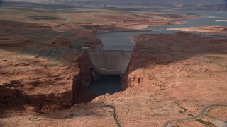 AX131_223 - 6K stock footage aerial video of flying by Lake Powell in the distance behind Glen Canyon Dam and Bridge, Arizona