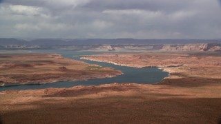 AX131_226 - 6K aerial stock footage video of passing by Lake Powell and distant mesas, Utah, Arizona