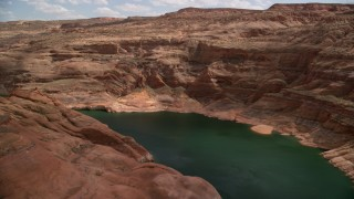 AX131_239 - 6K stock footage aerial video of flying over Lake Powell, pan across cliffs in Navajo Canyon, Arizona