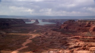 AX132_008 - 6K stock footage aerial video of flying by buttes, Lake Powell in the distance, Navajo Nation Reservation, Arizona