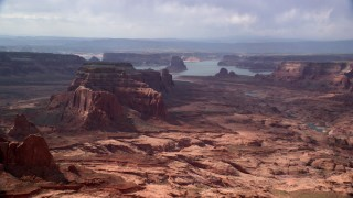 AX132_011 - 6K stock footage aerial video of flying by buttes, Lake Powell in the background, Navajo Nation Reservation, Arizona