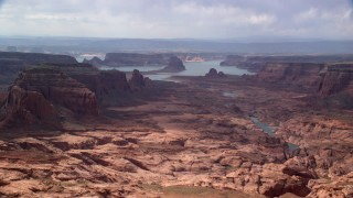 AX132_012 - 6K stock footage aerial video of passing by buttes leading to Lake Powell, Navajo Nation Reservation, Arizona