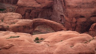 AX132_046 - 6K stock footage aerial video of flying by top of natural stone bridge, Rainbow Bridge National Monument, Utah