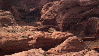 AX132_052 - 6K stock footage aerial video of flying by a stone arch at Rainbow Bridge National Monument, Utah