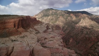 AX132_069 - 6K stock footage aerial video of flying by mountain peak, slopes, Navajo Mountain, Utah
