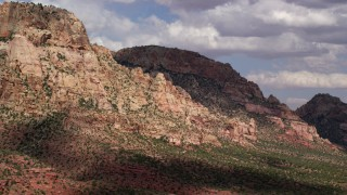 AX132_073 - 6K stock footage aerial video of flying by a mountain peak with rocky slopes, Navajo Mountain, Utah