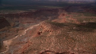 AX132_084 - 6K stock footage aerial video of passing by dry riverbed in desert canyon, Navajo Nation Reservation, Arizona, Utah