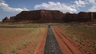 AX132_136 - 6K stock footage aerial video of approaching airport by Rock Door Mesa, Monument Valley Airport, Utah