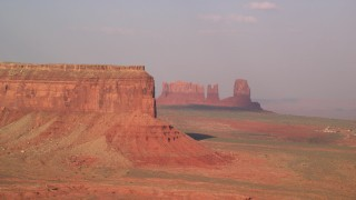 AX133_003 - 6K stock footage aerial video of the side of Eagle Mesa and buttes, Monument Valley, Utah, Arizona, sunset