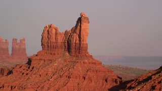 AX133_007 - 6K stock footage aerial video of passing by Setting Hen Butte, Monument Valley, Utah, Arizona, sunset