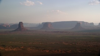 AX133_018 - 6K stock footage aerial video of a wide view of buttes, mesas across desert valley, Monument Valley, Utah, Arizona, twilight