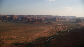 AX133_035 - 6K stock footage aerial video of approaching buttes, mesas across desert, Monument Valley, Utah, Arizona, twilight