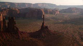 AX133_038 - 6K stock footage aerial video of flying by Totem Pole Butte, Monument Valley, Utah, Arizona, twilight