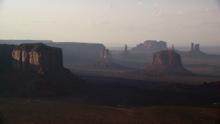 AX133_065 - 6K stock footage aerial video of buttes in a desert valley, Monument Valley, Utah, Arizona, twilight