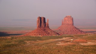 AX133_082 - 6K stock footage aerial video of flying by West and East Mitten Buttes, Monument Valley, Utah, Arizona, twilight
