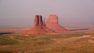 AX133_083 - 6K stock footage aerial video of passing by West and East Mitten Buttes, Monument Valley, Utah, Arizona, twilight