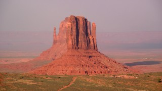 AX133_084 - 6K stock footage aerial video flyby West Mitten Butte to reveal East Mitten Butte, Monument Valley, Utah, Arizona, twilight