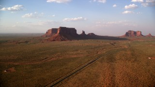 AX133_087 - 6K stock footage aerial video of flying over highway, approaching buttes in Monument Valley, Utah, Arizona, twilight
