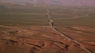 AX133_098 - 6K stock footage aerial video of Highway 163 through desert valley, Monument Valley, Utah, Arizona, twilight