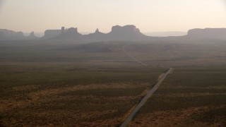 AX133_100 - 6K stock footage aerial video of flying by Highway 163 with view of buttes, mesas, Monument Valley, Utah, Arizona, twilight