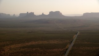 AX133_101 - 6K stock footage aerial video of a view of highway leading to buttes, mesas in Monument Valley, Utah, Arizona, twilight