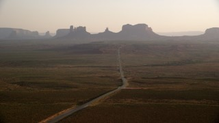 AX133_103 - 6K stock footage aerial video of passing by highway leading to buttes, mesas, Monument Valley, Utah, Arizona, twilight