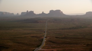 AX133_104 - 6K stock footage aerial video fly over highway, approach buttes and mesas, Monument Valley, Utah, Arizona, twilight