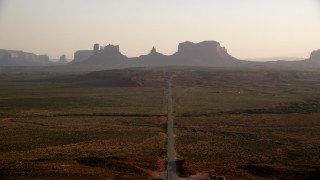 AX133_106 - 6K stock footage aerial video of following highway toward buttes, Monument Valley, Utah, Arizona, twilight