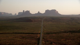 AX133_107 - 6K stock footage aerial video follow highway toward buttes in Monument Valley, Utah, Arizona, twilight