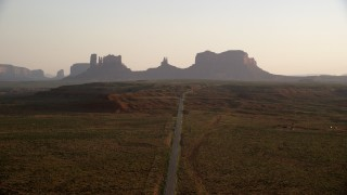 AX133_109 - 6K stock footage aerial video fly over highway and approach buttes, Monument Valley, Utah, Arizona, twilight