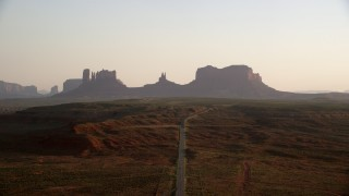 AX133_110 - 6K stock footage aerial video of ascend over highway, approaching buttes, Monument Valley, Utah, Arizona, twilight