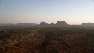 AX133_114 - 6K stock footage aerial video of highway to mesas and buttes, Monument Valley, Utah, Arizona, twilight
