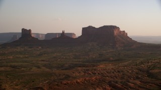 AX133_119 - 6K aerial stock footage video of passing by buttes and highway, Monument Valley, Utah, Arizona, twilight