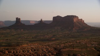 AX133_120 - 6K stock footage aerial video of a wide view of buttes and highway in Monument Valley, Utah, Arizona, twilight