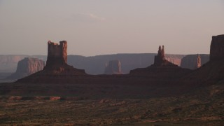 AX133_121 - 6K stock footage aerial video of flying by buttes on a hazy day, Monument Valley, Utah, Arizona, twilight