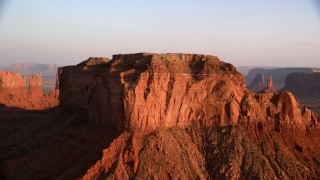AX133_128 - 6K stock footage aerial video of approaching top of Brighams Tomb Butte, Monument Valley, Utah, Arizona, twilight