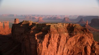 AX133_129 - 6K stock footage aerial video of fly over butte, revealing more buttes in Monument Valley, Utah, Arizona, twilight