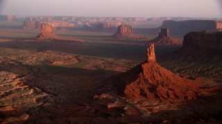 AX133_133 - 6K stock footage aerial video approach Big Indian Butte, view of nearby buttes, Monument Valley, Utah, Arizona, twilight