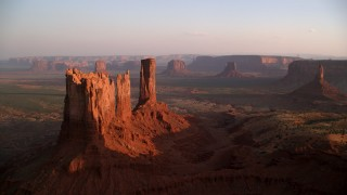 AX133_148 - 6K stock footage aerial video of an approach to buttes in famous Monument Valley, Utah, Arizona, sunset