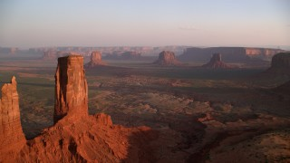 AX133_150 - 6K stock footage aerial video of flying by buttes and mesas in famous Monument Valley, Utah, Arizona, sunset