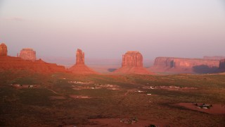 AX133_163 - 6K stock footage aerial video flyby buttes in a desert valley, Monument Valley, Utah, Arizona, sunset